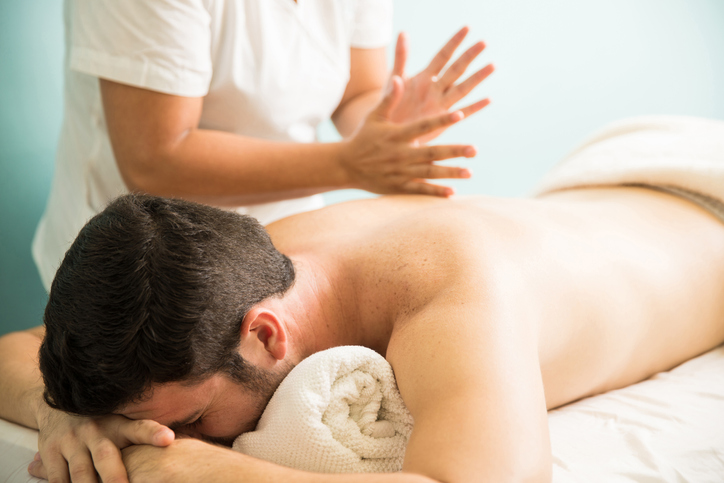 Closeup of a female therapist striking the back of a man using a tapotement massage technique in a spa